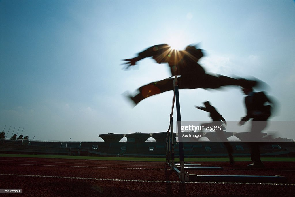 Silhouette of businessmen leaping hurdle : Stock Photo