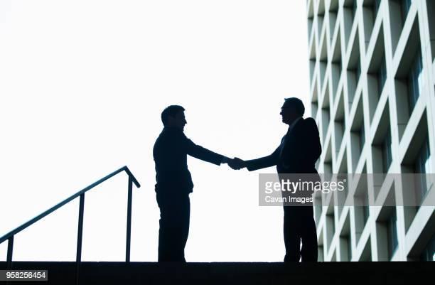 Silhouette of businessmen shaking hands against sky
