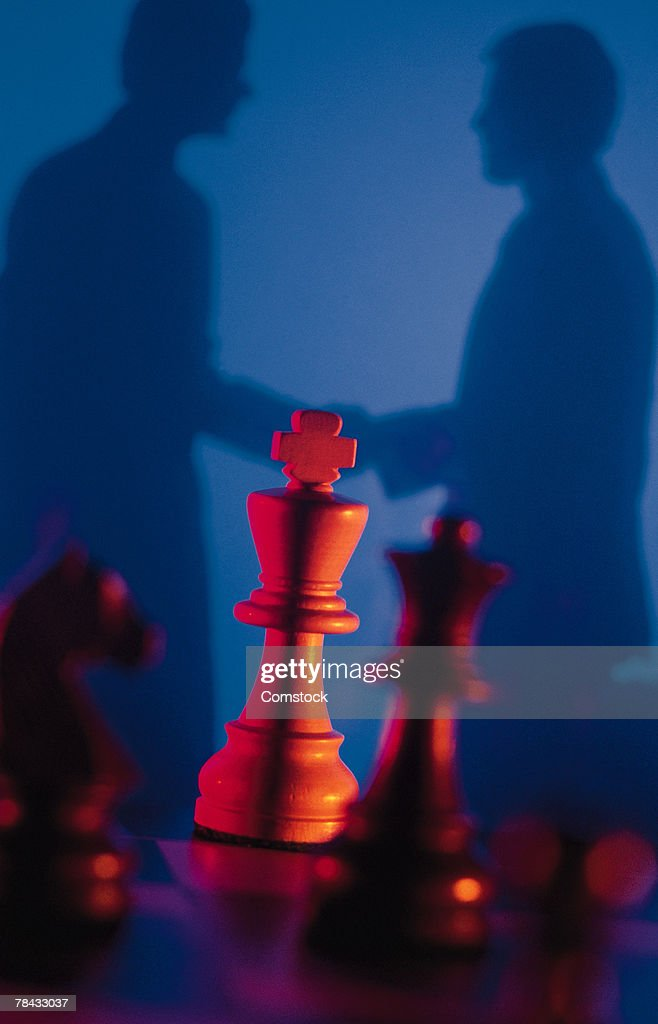 Silhouette of businessmen with chess pieces in foreground : Stockfoto