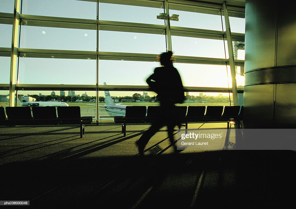 Silhouette of businessperson hurrying through airport terminal. : Stockfoto