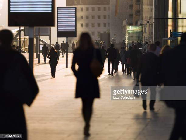 Silhouette of businesswoman among other commuters at modern business district