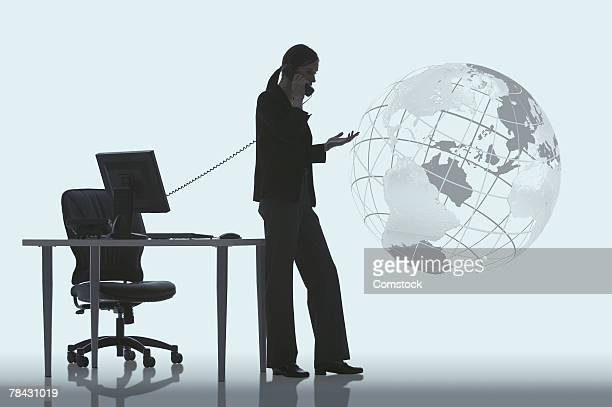 Silhouette of businesswoman talking on telephone near globe