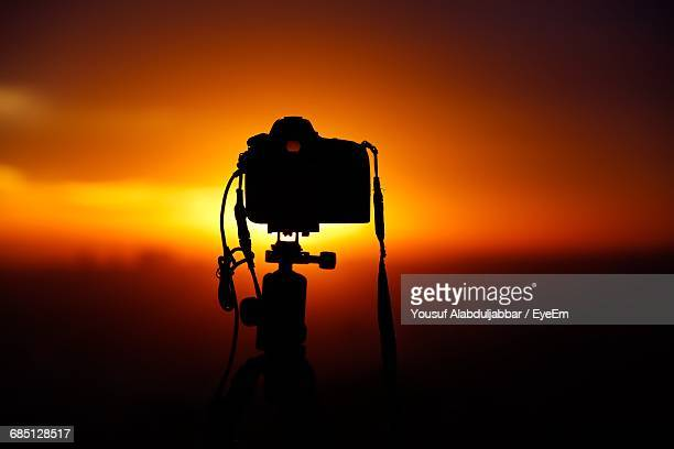 Silhouette Of Camera Pointing Towards Sunset