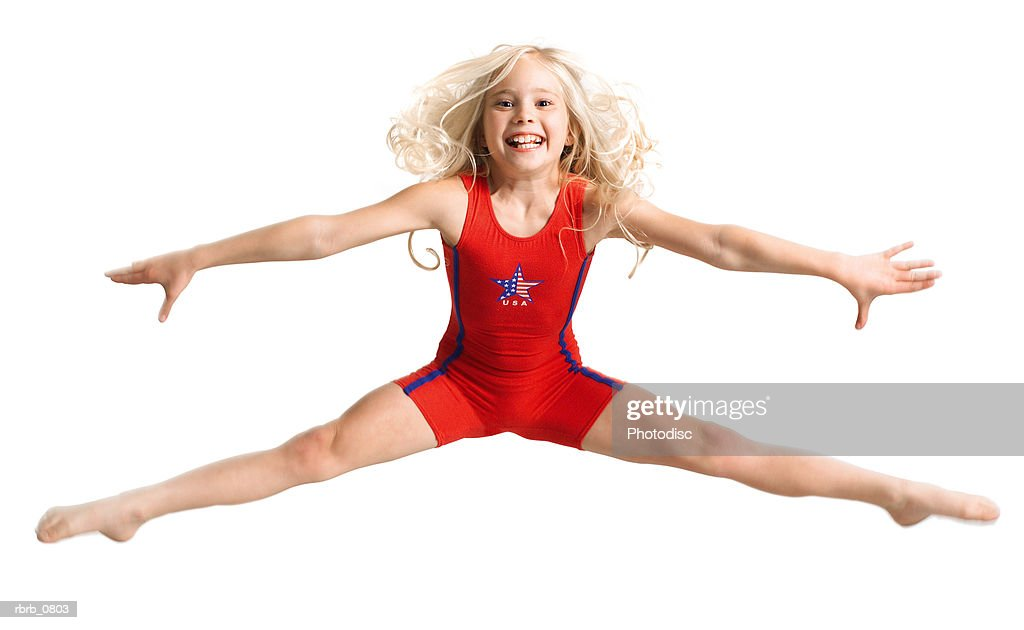 silhouette of caucasian blonde female child dancer in a red outfit as she jumps and does the splits : Stockfoto