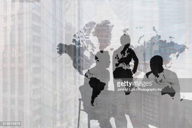 silhouette of caucasian business people near world map and cityscape - global - fotografias e filmes do acervo