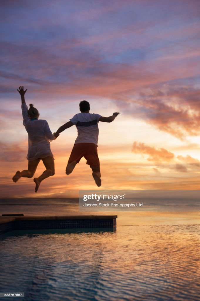 Silhouette of Caucasian couple jumping into swimming pool at sunset : Foto stock