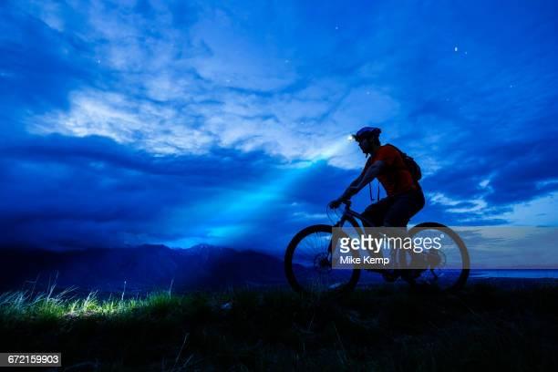 Silhouette of Caucasian man riding mountain bike at night