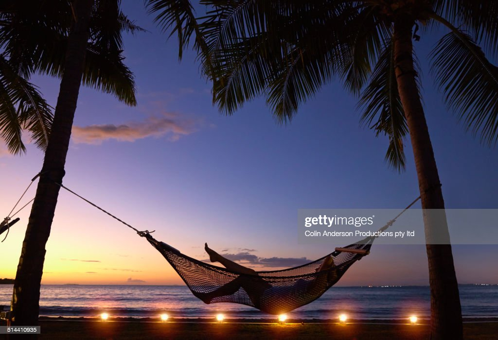 Silhouette of Caucasian woman relaxing in hammock at sunset : Stock Photo
