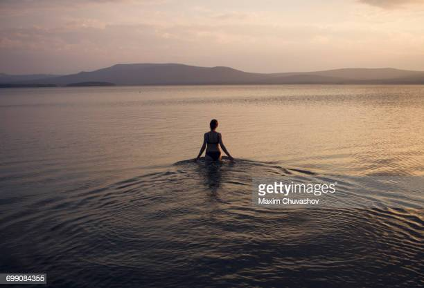 silhouette of caucasian woman wading in lake - wading stock pictures, royalty-free photos & images