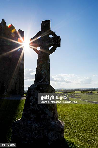 Silhouette of celtic cross with sunburst and castle tower in background