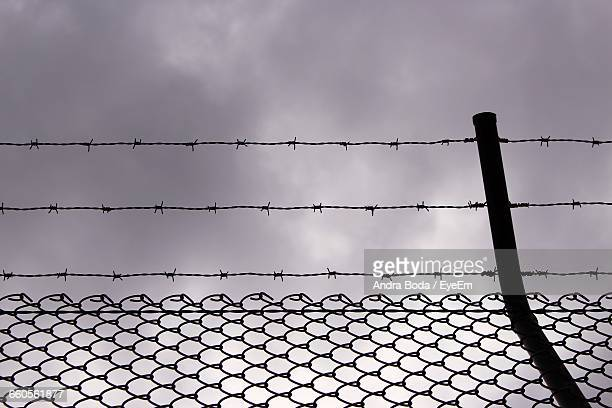 Silhouette Of Chain-Link Fence With Barbed Wire Against Cloudy Sky