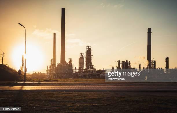 silhouette der chemieanlage bei sonnenuntergang - industriegebiet stock-fotos und bilder