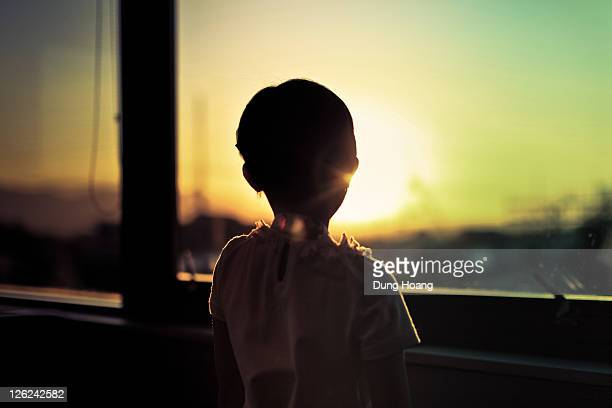 Silhouette of child by window looking at sunset