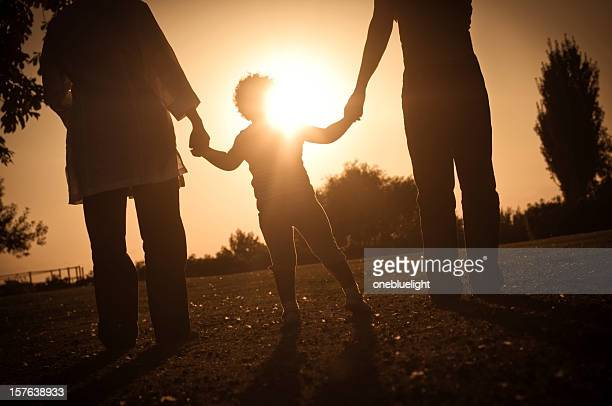 Silhouette of Child holding her mother's and grandmother's hands