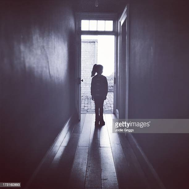 Silhouette of child standing alone in hallway