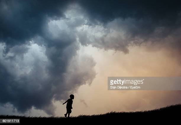Silhouette Of Child With Clouds In Sky