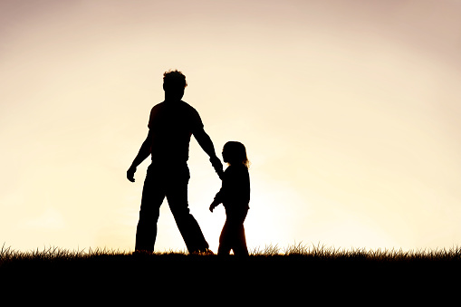Silhouette of Christian Father Guiding his Young Child by the Hand 1151242947