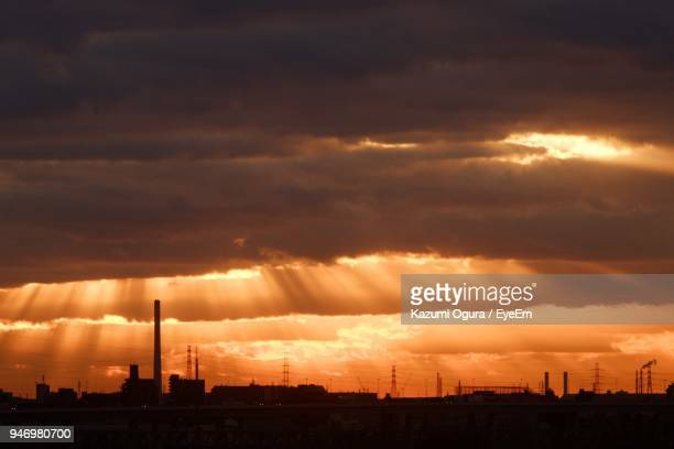 Silhouette Of City Against Cloudy Sky During Sunset