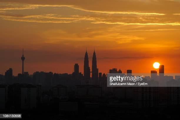 Silhouette Of Cityscape Against Sky At Sunset