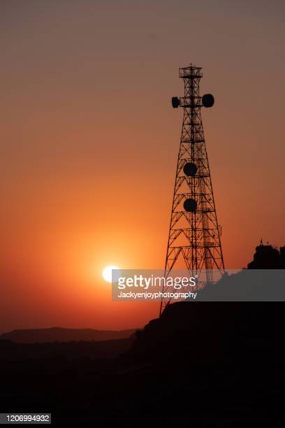 silhouette of communication tower for broadcasting during sunrise time. - tower stock pictures, royalty-free photos & images