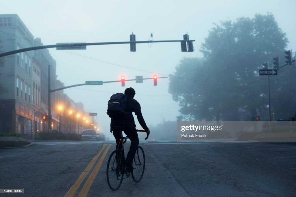 Silhouette of commuter riding bike during misty early morning : Stock-Foto