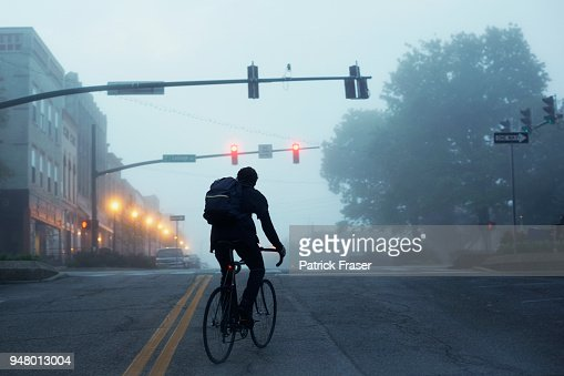 Silhouette of commuter riding bike during misty early morning