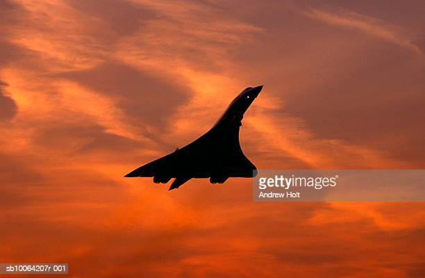 Silhouette of Concorde supersonic airplane against sunset sky