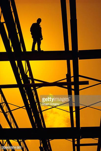 Silhouette of construction worker on girder, low angle view
