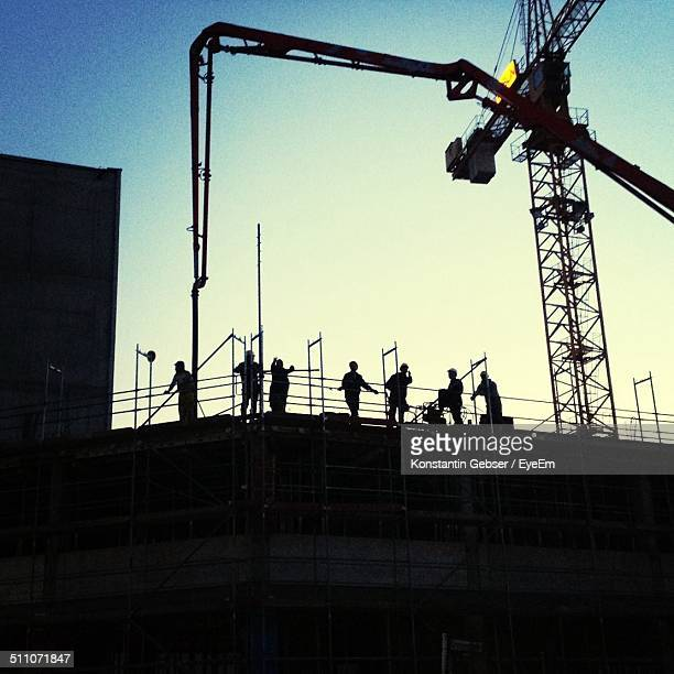 Silhouette of construction workers at site