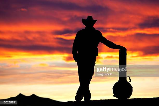 silhouette of country musician in dramatic sunset - traditional musician stock photos and pictures