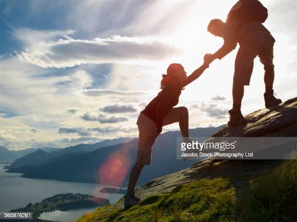 Silhouette of couple climbing hillside near remote lake