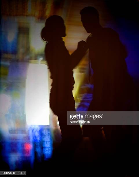 Silhouette of couple dancing, projected background