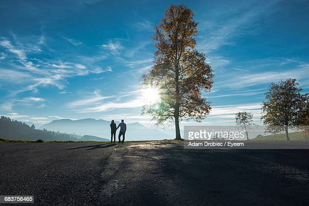 silhouette of couple on road against sky - mid distance stock pictures, royalty-free photos & images