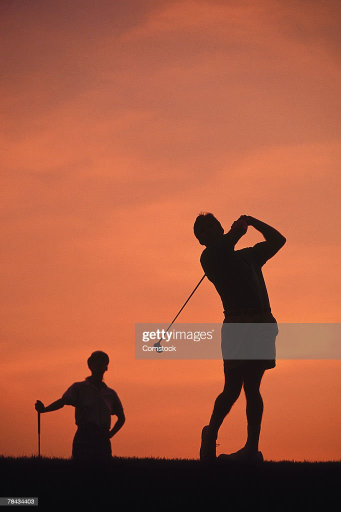 Silhouette of couple playing golf : Stockfoto