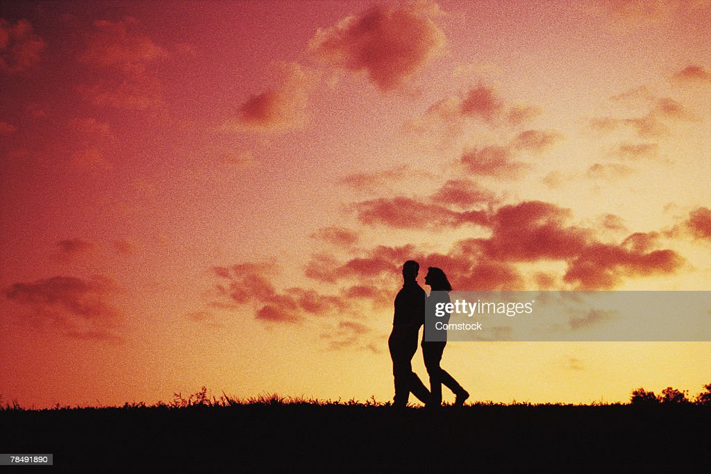 Silhouette of couple walking at dusk : Stock Photo