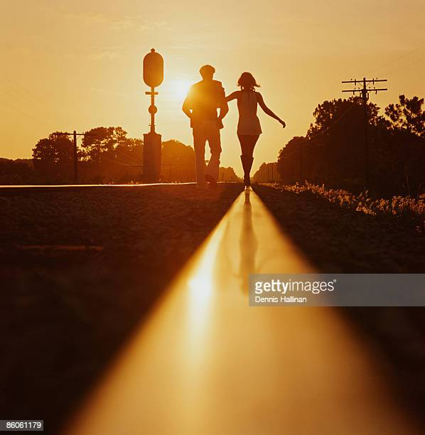 Silhouette of couple walking on railroad tracks at sunset