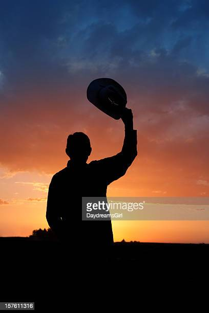 Silhouette of Cowboy viendo la puesta de sol