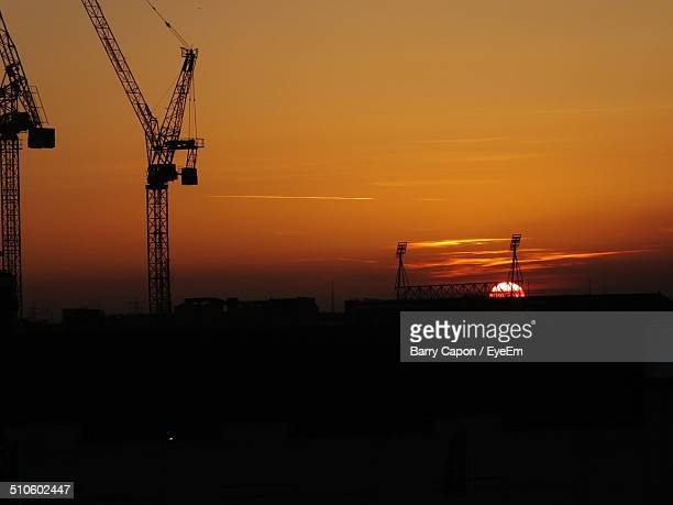 silhouette of cranes against sky at sunset - barry crane stock photos and pictures