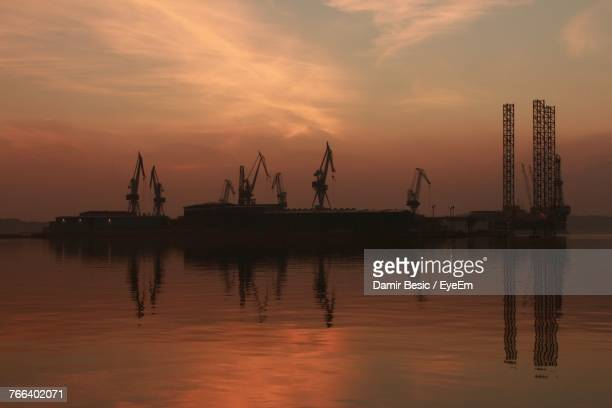 Silhouette Of Cranes At Harbor During Sunset