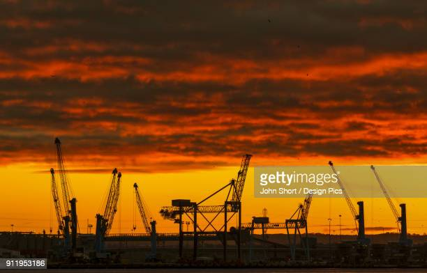 Silhouette Of Cranes On A Construction Site Against A Dramatic Red And Yellow Sky At Sunset