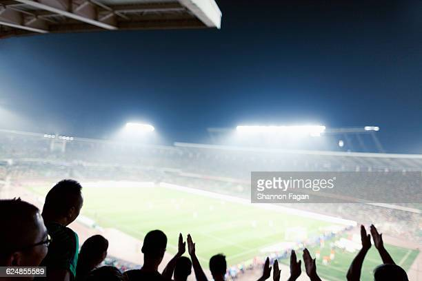 Silhouette of crowd cheering in stadium at night