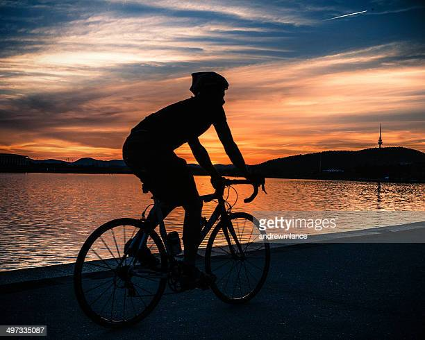 silhouette of cyclist at sunset near lake burley griffin, canberra, australia - canberra stock pictures, royalty-free photos & images