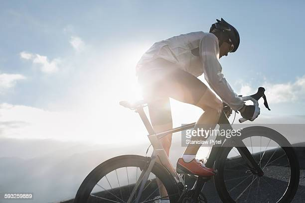 Silhouette of cyclist riding up in high mountains