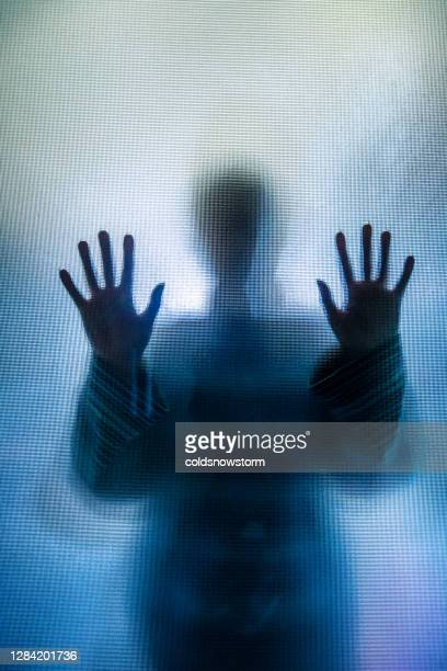 silhouette of depressed abused woman with hands pressed against glass - crime stock pictures, royalty-free photos & images