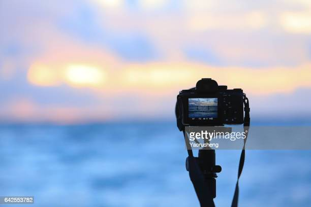 Silhouette of digital camera on tripod with sunset sky at sea