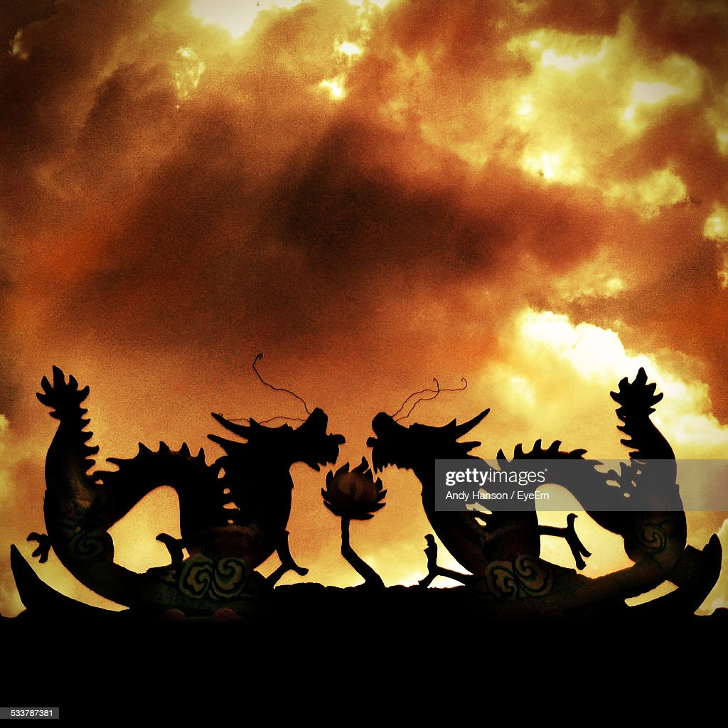 Silhouette Of Dragons Against Dramatic Sky : Foto stock