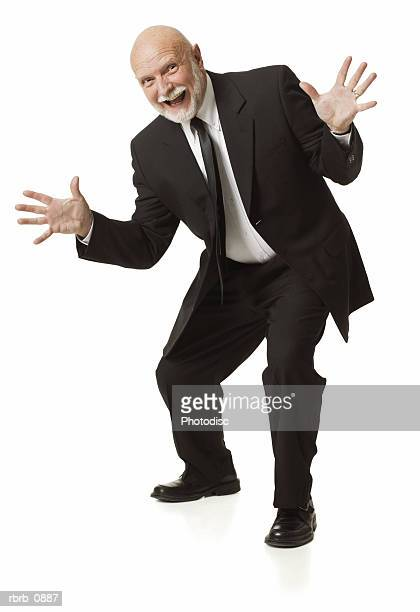 silhouette of elderly caucasian business man in black suit holds up his hands flashes a funny face