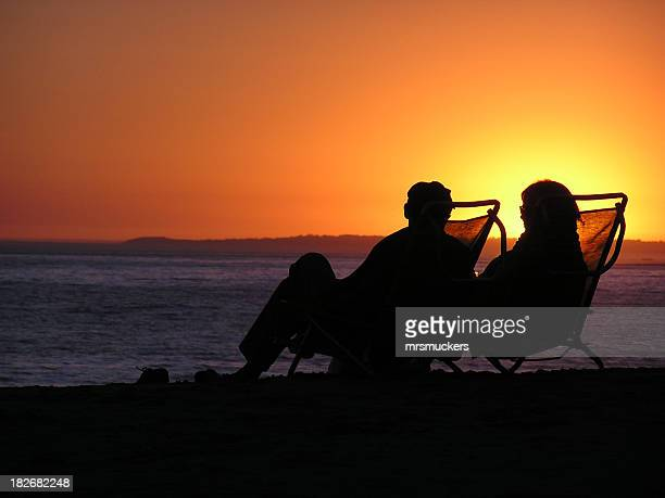 Silhouette of elderly couple sitting in deckchairs on beach