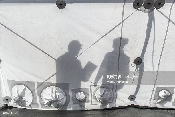 silhouette of emergency response team workers inside control centre tent - monty shadow stock photos and pictures