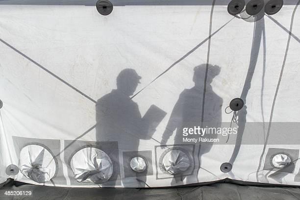 silhouette of emergency response team workers inside control centre tent - monty shadow - fotografias e filmes do acervo